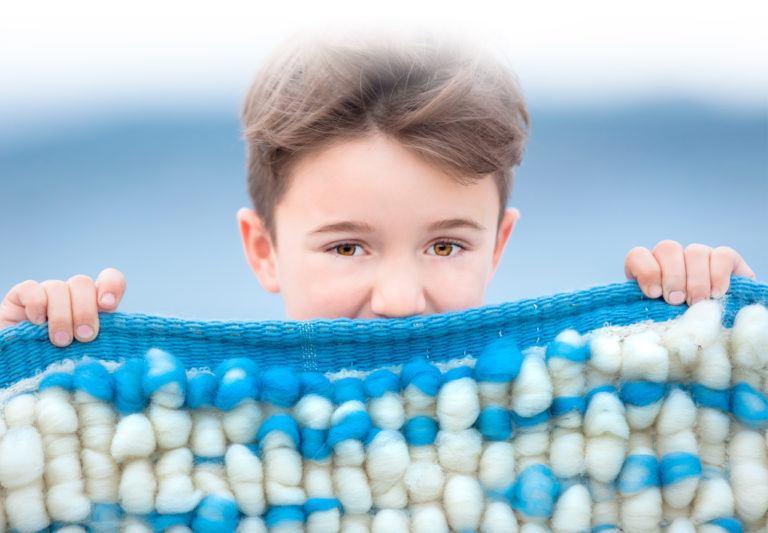 Niño de ojos marrones y pelo castaño sosteniendo tapiz artesanal de lana suave y cálido