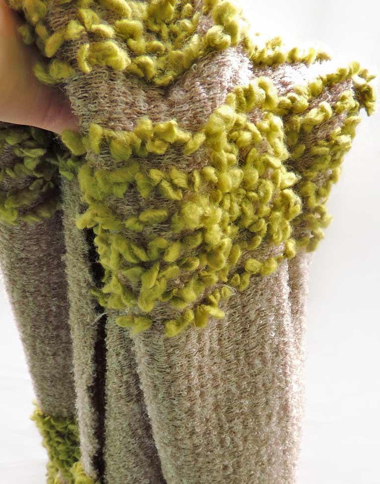 Detalle de la manta artesanal colección Fueguitos en lana merina verde y marrón