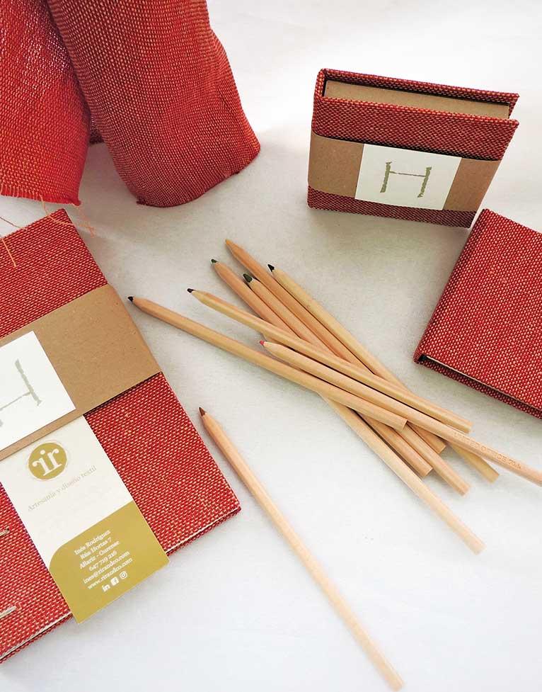 Libreta en color rojo y lápices con un toque artesanal