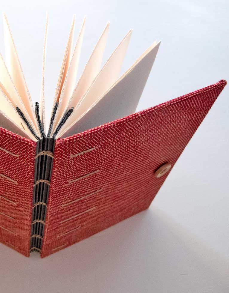Detalle de cuaderno con encuadernación artesanal y cubiertas tejidas a mano en lino