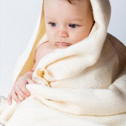Bebé envuelto en manta artesanal para bebé tejida con fibras de leche ecológicas