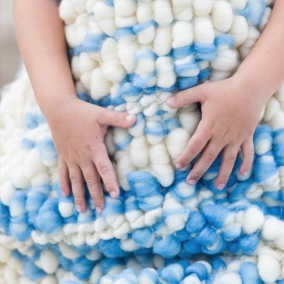 Manos sobre tapiz artesanal realizado en lana merina y lino